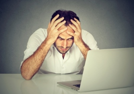 Stressed man sitting at his desk in front of computer